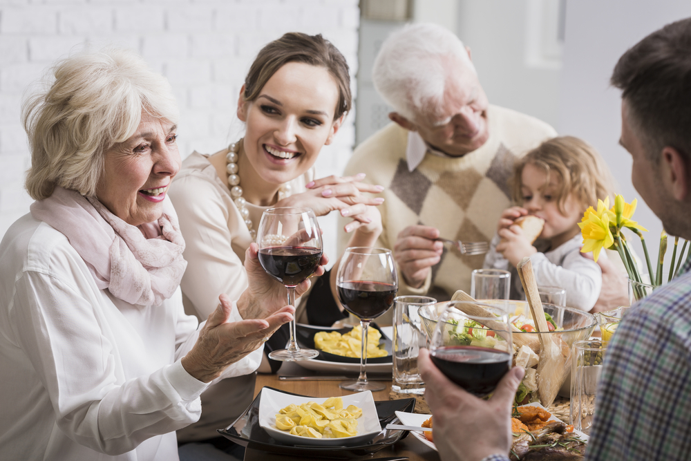 Elegant dinner of a multigenerational family, with a grandmother raising her glass in a toast