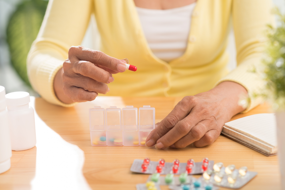 Hands of senior woman putting pills into pill box