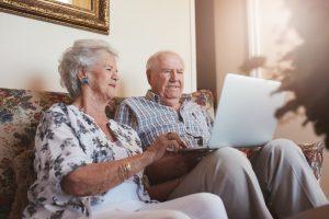 elderly-couple-sitting-on-sofa-using-laptop