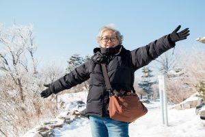 happy-smiling-asian-senior-woman-outside-in-the-snow-garden-at-yongpyong-ski-resort