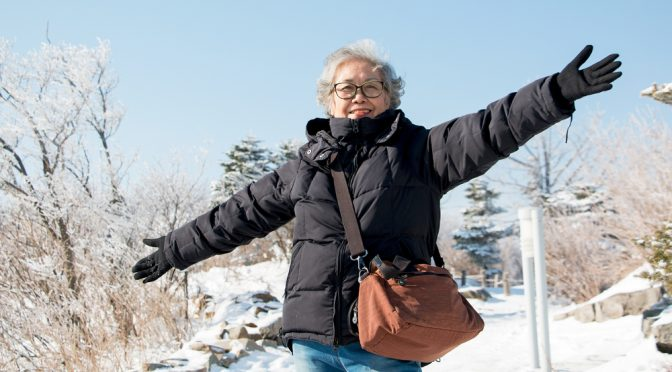 happy-smiling-asian-senior-woman-outside-in-the-snow-garden-at-yongpyong-ski-resort