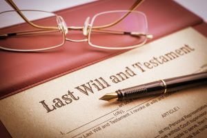 Fountain pen, eye glasses and a last will and testament on a vinyl desk pad. A form is printed on a mulberry paper and waiting to be filled and signed by testator