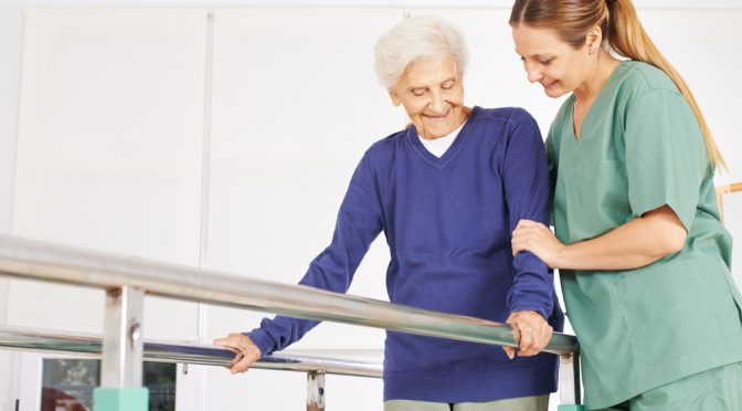 Physiotherapist helping old senior woman on treadmill with handles