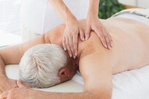 Female massage therapist massaging back of senior man in medical office