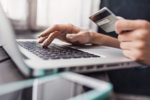 Hand holding credit card and using laptop