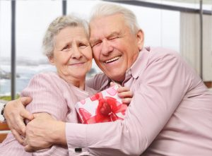 Smiling senior couple hugging at home, holding valentine's day gift