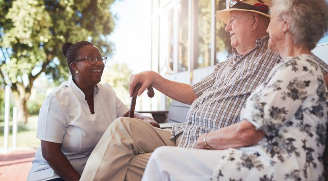 Portrait of senior couple relaxing on a bench outside their retirement home